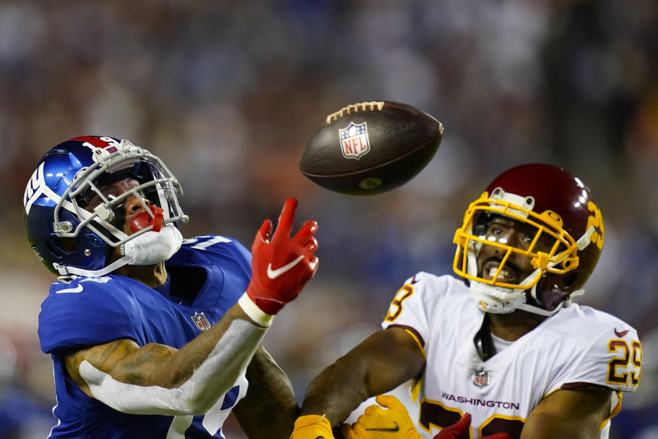 New York Giants wide receiver Kenny Golladay (19) looses control of the ball while being covered by Washington Football Team cornerback Kendall Fuller (29) during the second half of an NFL football game, Thursday, Sept. 16, 2021, in Landover, Md. (AP Photo/Patrick Semansky)