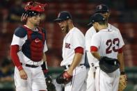 Boston Red Sox's Marcus Walden, center, reacts between teammates Kevin Plawecki, left, Xander Bogaerts, behind, and Michael Chavis (23) as manager Ron Roenicke comes to the mound for a pitching change during the fifth inning of a baseball game against the Tampa Bay Rays, Monday, Aug. 10, 2020, in Boston. (AP Photo/Michael Dwyer)