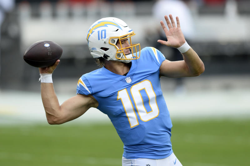 Justin Herbert leans back in a throwing motion in full Chargers uniform.