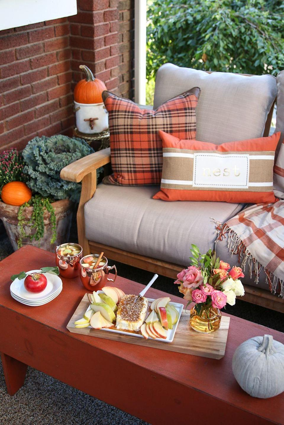 """<p><a href=""""https://www.elledecor.com/life-culture/entertaining/g10341591/garden-wedding-venues/"""" rel=""""nofollow noopener"""" target=""""_blank"""" data-ylk=""""slk:Outdoor entertaining"""" class=""""link rapid-noclick-resp"""">Outdoor entertaining</a> spaces deserve a fall touch too! Blogger Michael Wurm Jr. of <a href=""""http://inspiredbycharm.com/2016/09/fall-entertaining-around-my-house-tour.html"""" rel=""""nofollow noopener"""" target=""""_blank"""" data-ylk=""""slk:Inspired by Charm"""" class=""""link rapid-noclick-resp"""">Inspired by Charm</a> made his porch the perfect autumnal entertaining area by bringing the indoors out, with orange-and-brown throw pillows and blankets, a rust-colored coffee table, and some apple hors d'oeuvres and drinks.</p>"""