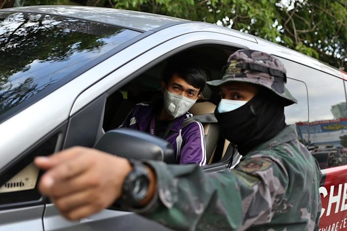 A masked solider is pictured talking to a driver in the island Luzon in the Philippines on 18 March. The Philippines has had 187 confirmed cases. (Getty Images)