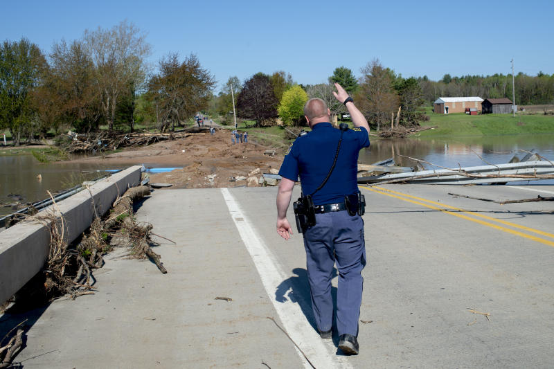 A Michigan State Police trooper waves off residents as they begin to gather to see the ruins of the Curtis Road Bridge on Wednesday, May 20, 2020 in Edenville Township north of Midland. After two days of heavy rain, the Edenville Dam failed and flood waters rushed south, ravaging the landscapre in its path. (Jake May/The Flint Journal, MLive.com via AP)