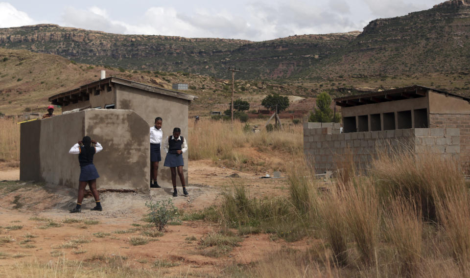 Girls stand near a pit latrine, at a school in Ghoboshiyane village, South Africa, Wednesday, March 17, 2021. A school headmaster in South Africa has been arrested and charged with child abuse after lowering an 11-year-old student into a pit latrine to search for the official's cellphone. According to local news reports, the headmaster of Luthuthu Junior Secondary School in the Eastern Cape province has been released on bail. (AP Photo)