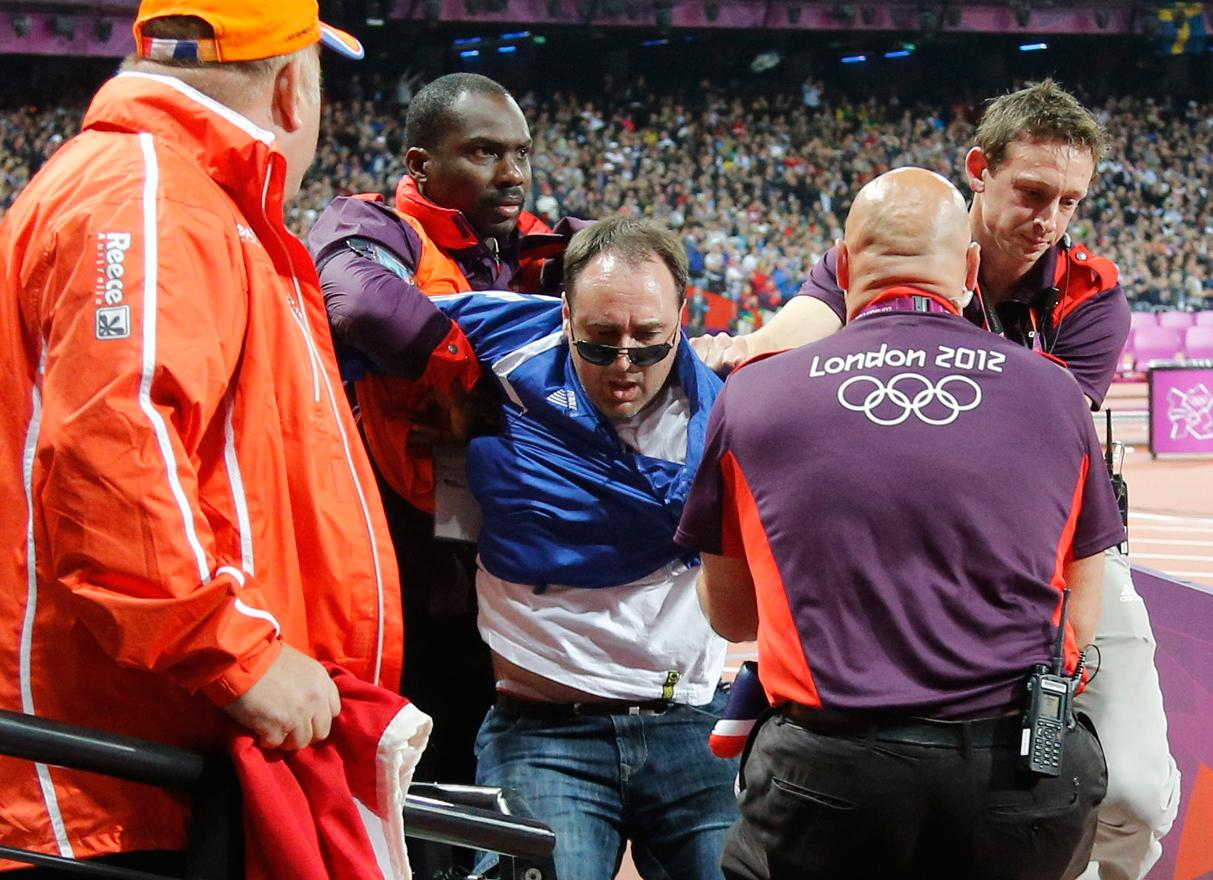 A spectator is detained by security after a beer bottle was thrown on to the track during the start of the men's 100 metres final, on Day 9 of the London 2012 Olympic Games at the Olympic Stadium on August 5, 2012 in London, England.  (Photo by Chris Helgren - IOPP Pool /Getty Images)