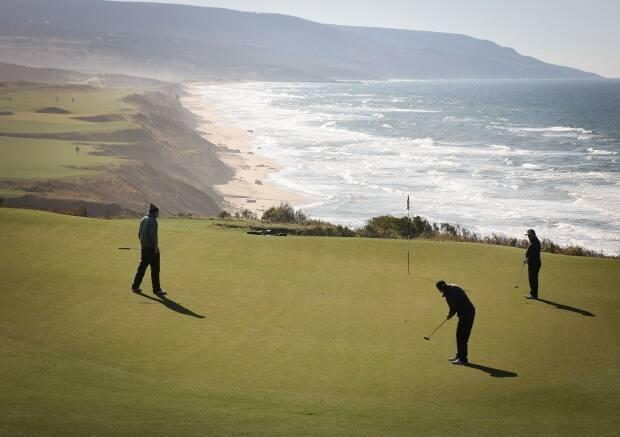 Golfers putt on the 17th green at the Cabot Cliffs golf course in Inverness, N.S.