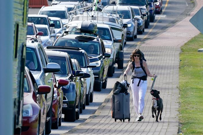 Terri Mills and her dog, Carlos, walk past a line of vehicles waiting to enter Canada at the Peace Arch border crossing in Blaine, Washington on Aug. 9. Mills, an American from Grizzly Flats, Calif., was heading to visit her Canadian husband after Canada opened its border to nonessential travel.