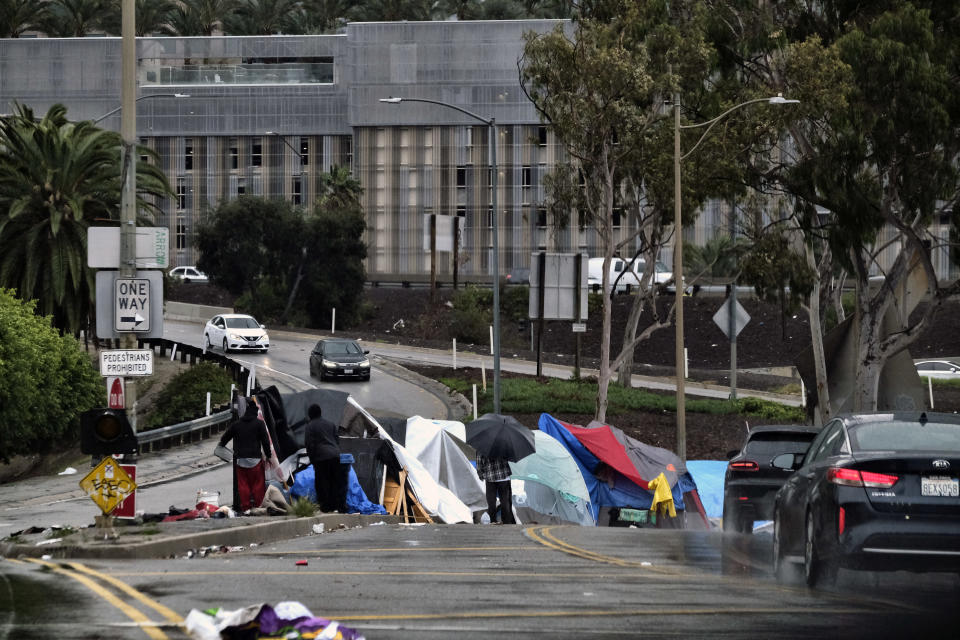 FILE - In this Jan. 14, 2019, file photo homeless shelter from a storm passing over downtown Los Angeles at their encampment along an offramp to the 110 freeway. A federal judge has ordered Los Angeles city and county to move thousands of homeless people who are living near freeways, saying their health is at risk from pollution and the coronavirus. (AP Photo/Richard Vogel, File)