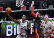 San Antonio Spurs guard Lonnie Walker IV, left, drives to the basket on Portland Trail Blazers center Jusuf Nurkic during the first half of an NBA basketball game in Portland, Ore., Saturday, May 8, 2021. (AP Photo/Steve Dykes)