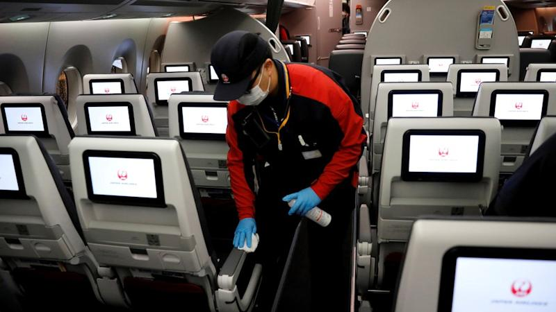 A staff member of Japan Airlines wearing a protective face mask and gloves cleans the cabin of a plane after performing a domestic flight
