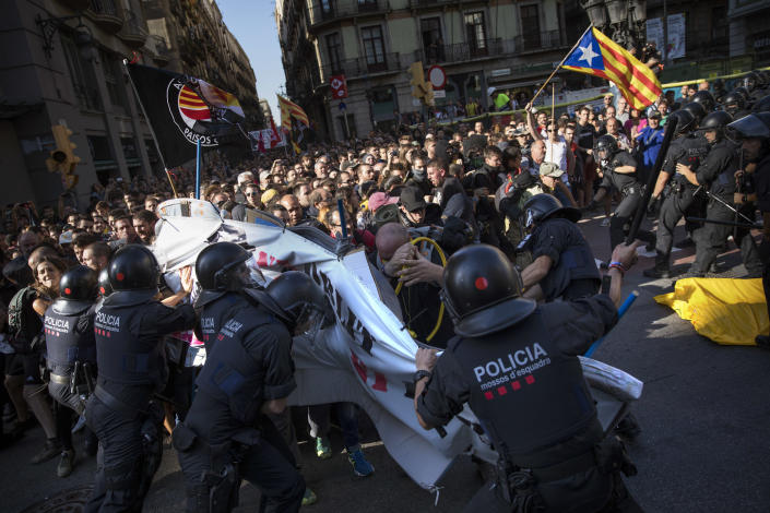 Catalan police officers clash with pro independence demonstrators on their way to meet a demonstrations of member and supporters of National Police and Guardia Civil in Barcelona on Saturday, Sept. 29, 2018. (AP Photo/Emilio Morenatti)
