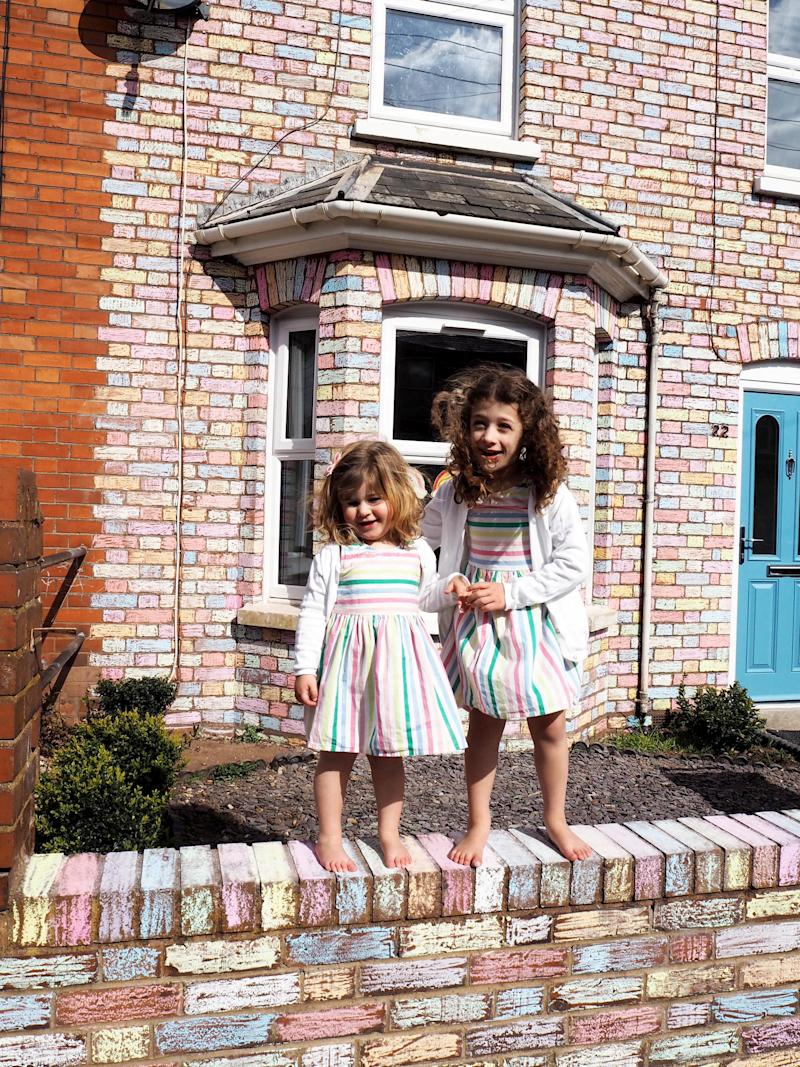 Matilda and Arabella don rainbow dresses to match their rainbow house. (SWNS)