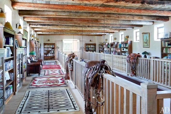 """<p>This """"galleria"""" is upstairs in the River House. The saddle closest to the camera was that of actress Greer Garson, who owned Forked Lightning for years with her Texas oilman husband.<a href=""""http://archdg.st/1oYTZR3"""" rel=""""nofollow noopener"""" target=""""_blank"""" data-ylk=""""slk:Click here to read more about Jane Fonda's ranch"""" class=""""link rapid-noclick-resp""""> Click here to read more about Jane Fonda's ranch</a> on ArchitecturalDigest.com, and <a href=""""http://archdg.st/1oZ5IPj"""" rel=""""nofollow noopener"""" target=""""_blank"""" data-ylk=""""slk:click here to see more pictures on AD's site"""" class=""""link rapid-noclick-resp"""">click here to see more pictures on AD's site</a>.<i> (Photo: Simon Upton/Architectural Digest)</i> <br></p>"""
