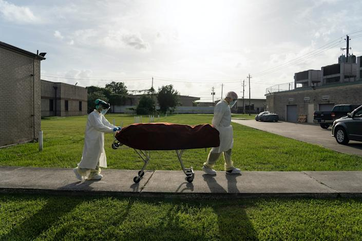 "Medical staff wearing PPE push a stretcher with a deceased patient to a car outside the COVID-19 intensive-care unit at United Memorial Medical Center in Houston, Texas, on June 30, 2020. <p class=""copyright"">Go Nakamura/Getty Images</p>"