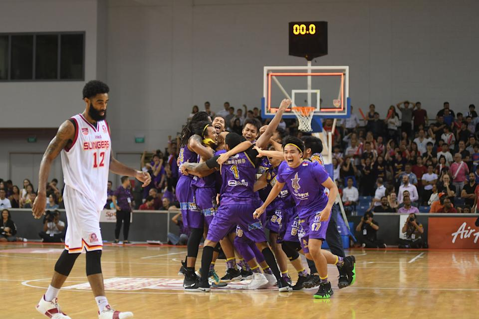 The CSL Knights Indonesia players celebrating their Asean Basketball League Finals win, as the Singapore Slingers' Jerran Young walks away from the OCBC Arena court. (PHOTO: Stefanus Ian/Yahoo News Singapore)