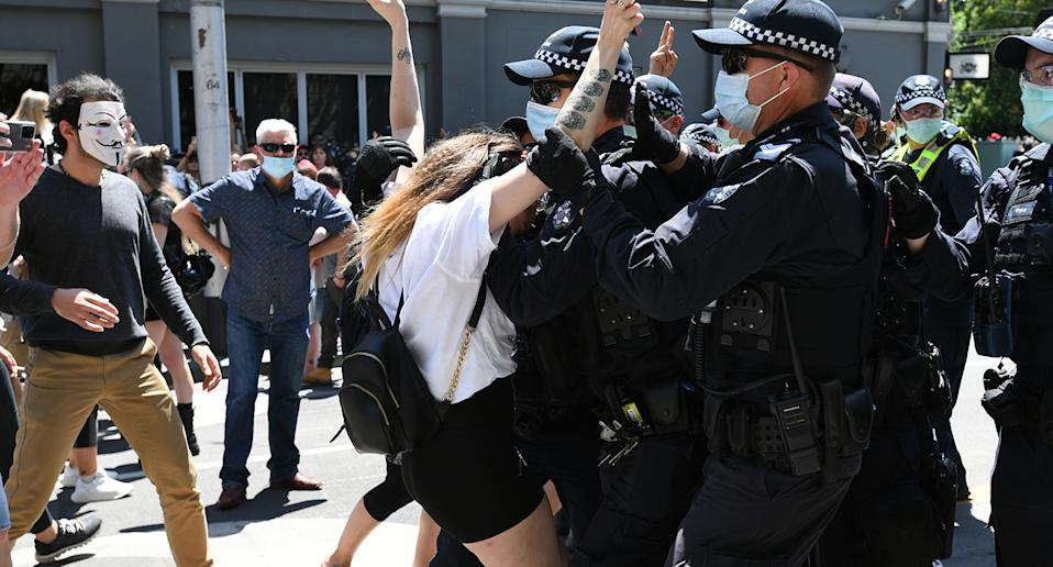 Protesters scuffle with police during an anti-lockdown protest in Melbourne, Tuesday, November 3, 2020.