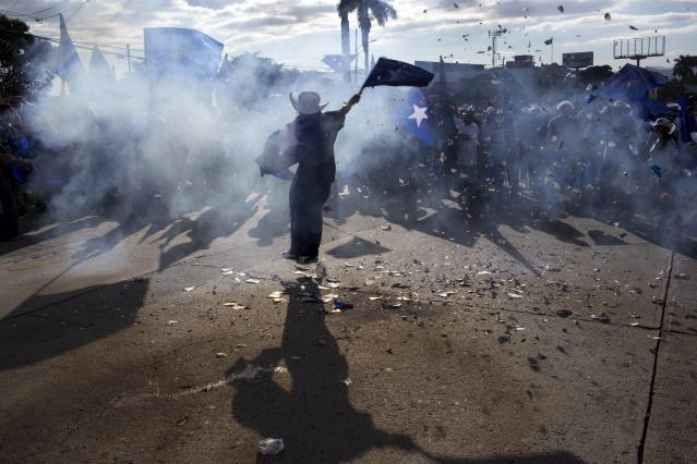 <p>A supporter of Honduran President Juan Orlando Hernandez, who is running for reelection, waves a flag amid smoke from firecrackers, during a march to show support for their candidate in Tegucigalpa, Honduras, Tuesday, Nov. 28, 2017. (Photo: Rodrigo Abd/AP) </p>