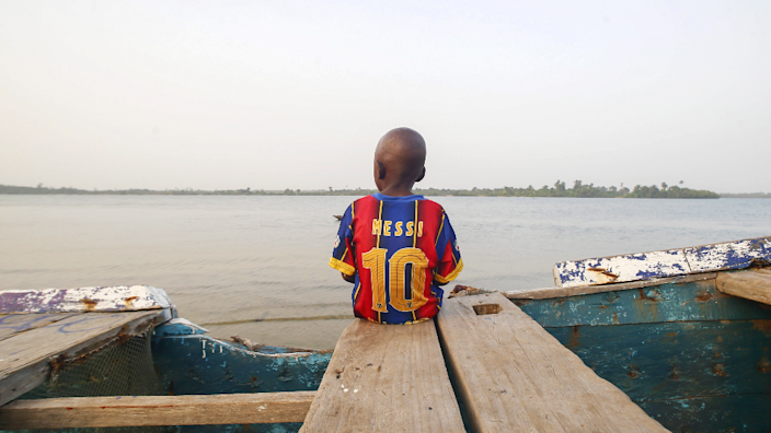 A boy sits on a fishing boat staring out at to sea with his back to the camera wearing a shirt with the number 10 of Lionel Messi, the Barcelona football player in Grand Cape Mount County, Liberia - Saturday 20 March 2021