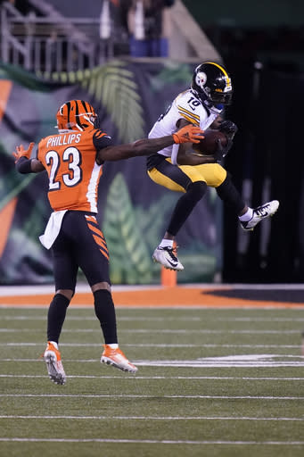 Pittsburgh Steelers' Diontae Johnson (18) makes a catch against Cincinnati Bengals' Darius Phillips (23) during the first half of an NFL football game, Monday, Dec. 21, 2020, in Cincinnati. (AP Photo/Bryan Woolston)