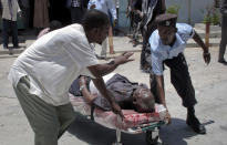 Somalis evacuate a man wounded in a blast at the Somali National Theater in Mogadishu, Somalia Wednesday, April 4, 2012. A suicide blast during a ceremony at Somalia's newly reopened national theater on Wednesday killed at least 10 people, including two of the country's top sports officials, officials said. (AP Photo/Mohamed Sheikh Nor)