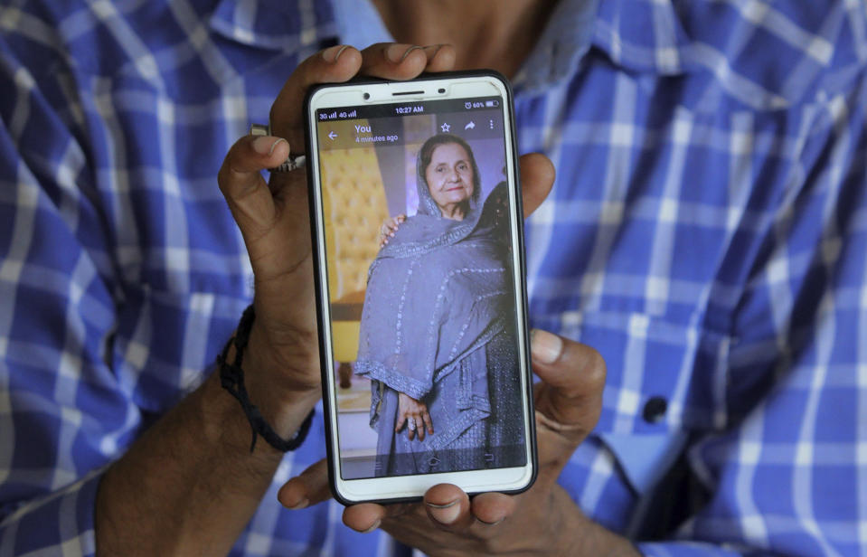 Pakistani Shahid Ahmed shows the picture of his mother Irshad Begum, who was killed in the Friday's plane crash, on his mobile phone outside a morgue in Karachi, Pakistan, Saturday, May 23, 2020. An aviation official says a passenger plane belonging to state-run Pakistan International Airlines carrying passengers and crew has crashed near the southern port city of Karachi. (AP Photo/Fareed Khan)