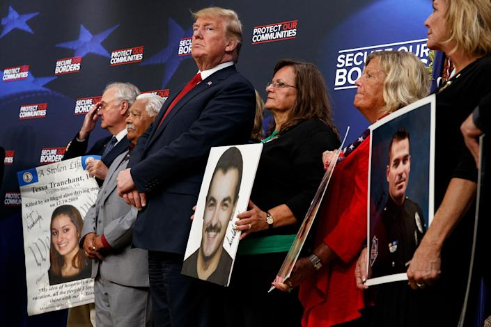 """Former President Donald Trump stands alongside """"angel families"""" at the White House complex on June 22, 2018."""
