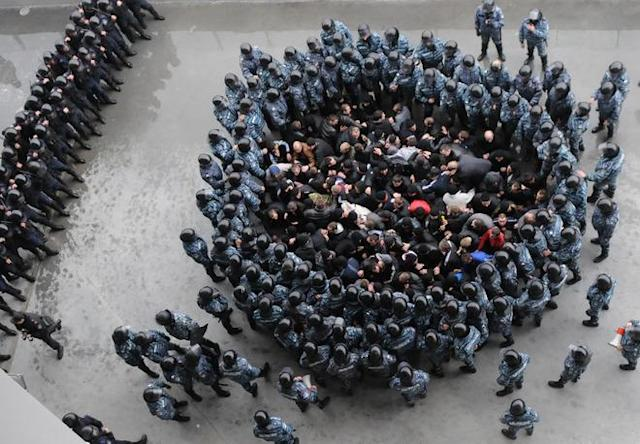 "TOPSHOTS Riot policemen block ""football hooligans"" during an exercise at Arena Lviv stadium in western Ukrainian city of Lviv on April 19, 2012, in the network of preparation for EURO-2012. (Photo by Yuriy Dyachyshyn /AFP/Getty Images)"