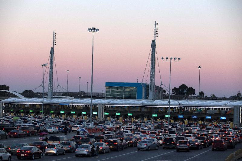 Thousands of people stream over pedestrian bridges in both directions around the clock at the San Ysidro border crossing as long lines of cars queue for inspection to enter the US (AFP Photo/GUILLERMO ARIAS)