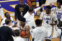 LSU guard Cameron Thomas, holding the ball, celebrates with head coach Will Wade, center, and tamales forward Darius Days (4) and guard Eric Gaines (25) after an NCAA college basketball game in Baton Rouge, La., Saturday, Feb. 13, 2021. (AP Photo/Gerald Herbert)