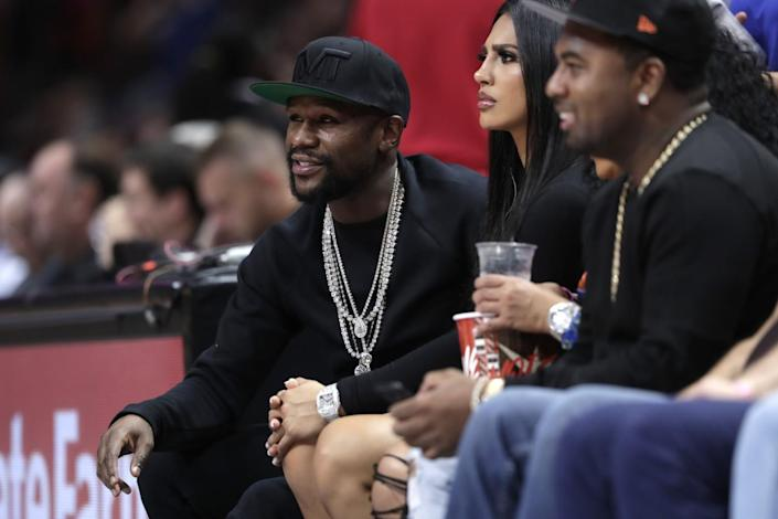 Floyd Mayweather, left, watches an NBA basketball game in Miami.