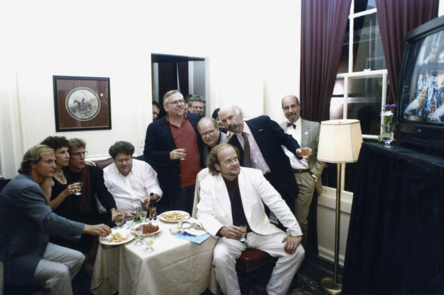 The cast and crew of <i>Cheers</i> gathers to watch the series finale. Pictured: (l-r) Woody Harrelson (Woody Boyd), Rhea Perlman (Carla LeBec), Ted Danson (Sam Malone), George Wendt (Norm Peterson), John Ratzenberger (Cliff Clavin), Paul Willson (Paul Krapence), Kelsey Grammer (Dr. Frasier Crane), and director/creator James Burrows (Photo: NBCU Photo Bank)