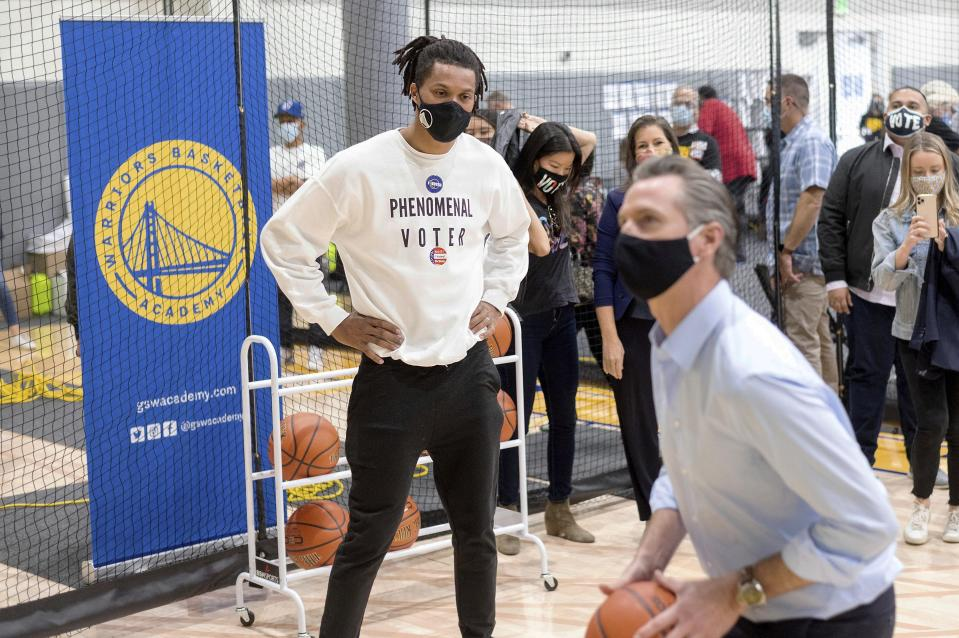 Golden State Warriors guard Damion Lee watches California Gov. Gavin Newsom shoot hoop during a visit to the team's training facility, which is serving as a polling location, on Tuesday, Nov. 3, 2020, in Oakland, Calif. (AP Photo/Noah Berger)