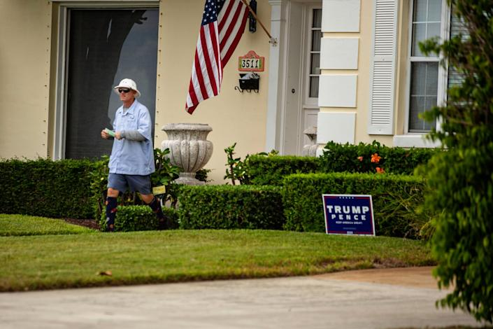 A postman leaves a West Palm Beach home with a yard sign for President Trump in the lawn.