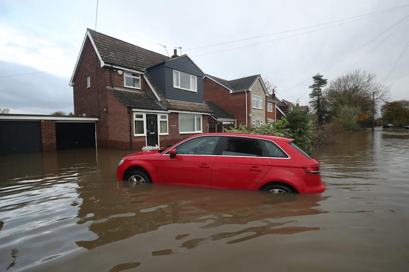 A car in floodwater outside a house in Fishlake, Doncaster. The Prime Minister is set to chair a meeting of the Government's emergency committee after severe flooding in parts of the country, where rain is finally expected to ease this afternoon.