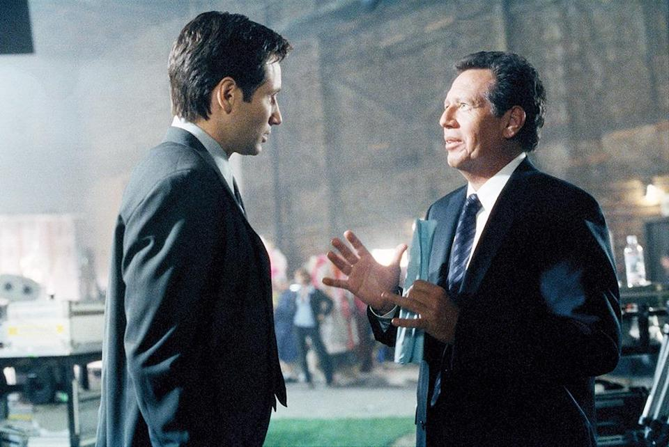 """<p>David Duchovny wrote and directed this highly tongue-in-cheek episode that featured Shandling and Téa Leoni as themselves playing big-screen versions of Mulder and Scully in a movie about one of the <i>real</i> Mulder and Scully cases. """"You cigarette-smoking mackerel snapper!"""" Shandling-as-Mulder <a href=""""https://www.youtube.com/watch?v=Sv_qYe6m8KA"""" rel=""""nofollow noopener"""" target=""""_blank"""" data-ylk=""""slk:trash talks at one point"""" class=""""link rapid-noclick-resp"""">trash talks at one point</a>. </p><p><i>(Credit: Everett Collection)</i></p>"""