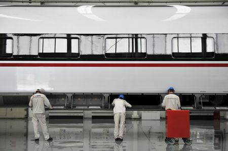 FILE PHOTO: Men work on a high-speed train at the CRRC Qingdao Sifang manufacturing base in Shandong