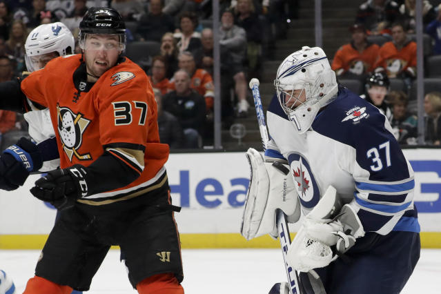 Winnipeg Jets goaltender Connor Hellebuyck blocks a shot as Anaheim Ducks left wing Nick Ritchie looks on during the second period of an NHL hockey game in Anaheim, Calif., Friday, Nov. 29, 2019. (AP Photo/Chris Carlson)