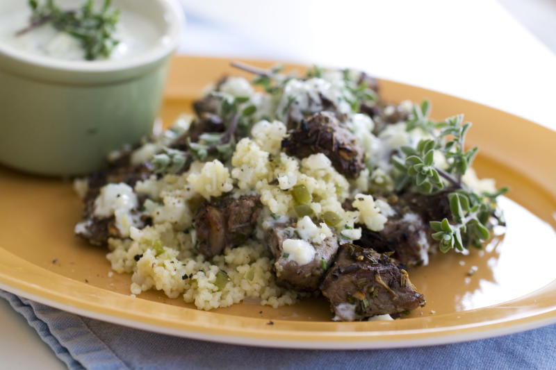 This image taken on April 22, 2013, shows lemon-garlic lamb kebabs with bell pepper couscous served on a plate in Concord, N.H. (AP Photo/Matthew Mead)