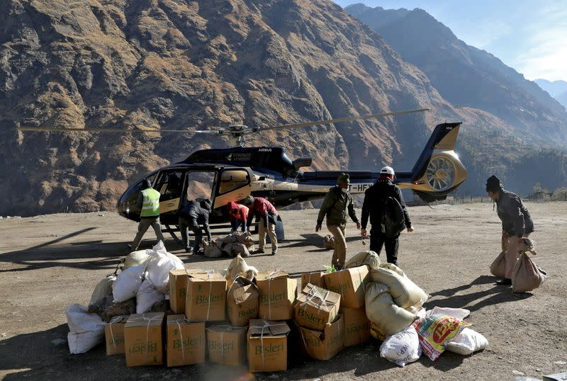 People load relief goods onto a helicopter for distribution in the affected areas, after a flash flood swept a mountain valley destroying dams and bridges, in Dhak village