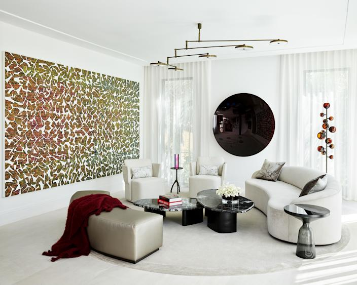 """<div class=""""caption""""> More of radio host Tom Joyner's enviable art collection is on display in his Golden Beach, Florida, living room, designed by Deborah Wecselman. The black Anish Kapoor mirror is so heavy that the wall behind it actually had to be reinforced before it could be hung. The large piece on the left is by Allora & Calzadilla and is made out of broken solar panel fragments. Wecselman opted for white and beige furniture to make the art pop even more: The sofa is custom designed by her; and the coffee tables, chairs, pendant light, and floor lamp are all sourced from <a href=""""https://www.hollyhunt.com/"""" rel=""""nofollow noopener"""" target=""""_blank"""" data-ylk=""""slk:Holly Hunt"""" class=""""link rapid-noclick-resp"""">Holly Hunt</a>. </div>"""