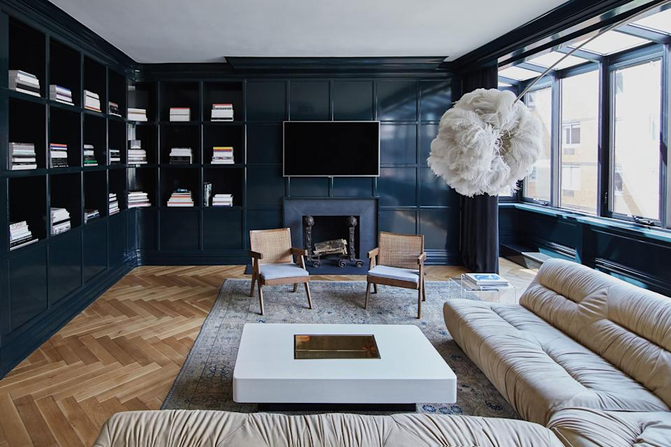 Inside the lacquered library. The cozy yet sexy sectional is a mid-1970s vintage find. Blinken included the ostrich feather lamp to add a playful note to the room. The Willy Rizzo coffee table in the center has a pearl finish; the chairs are Pierre Jeanneret.