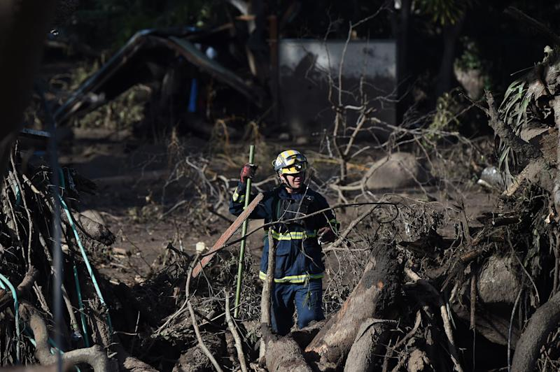 A member of the Orange County Urban Search and Rescue team looks for people missing in the aftermath of a massive mudslide in Montecito, California, earlier this week. (ROBYN BECK via Getty Images)