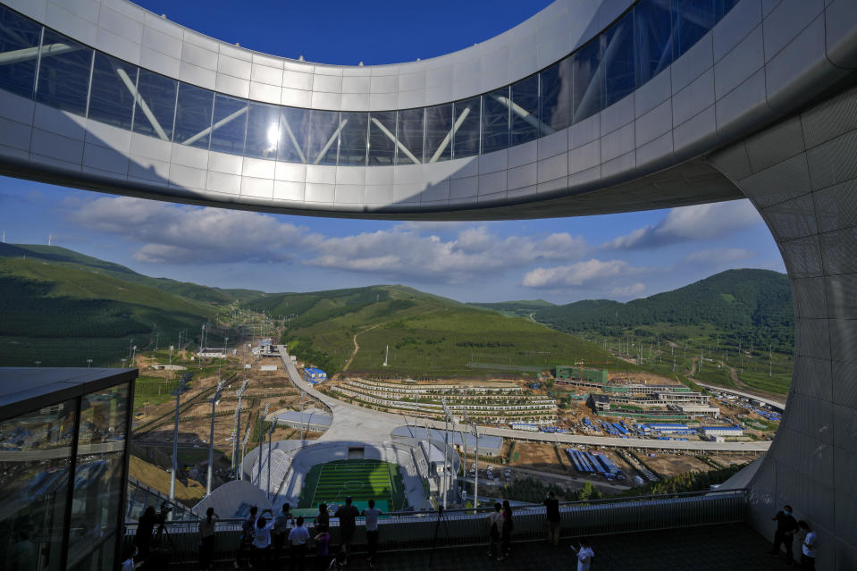 Chinese officials and journalists view the National Cross-Country Skiing Center, right, and National Biathlon Centre, left, from a platform of the National Ski Jumping Centre, one of the venues for Beijing 2022 Olympic and Paralympic Winter Games, during a media tour in Zhangjiakou in northwestern China's Hebei province on Wednesday, July 14, 2021. (AP Photo/Andy Wong)