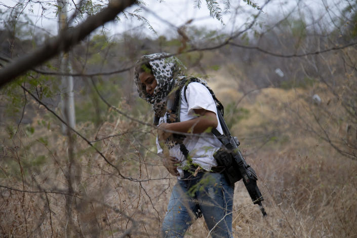 """An armed woman who goes by the nickname """"La Chola,"""" and who says she is a member of a female-led, self-defense group, patrols the edge of her town of El Terrero, where it shares a border with the town of Aguililla, in Michoacan state, Mexico, Thursday, Jan. 14, 2021. In the birthplace of Mexico's vigilante """"self-defense"""" movement, a new group has emerged entirely made up of women, who carry assault rifles and post roadblocks to fend off what they say is a bloody incursion into the state of Michoacán by the violent Jalisco cartel. (AP Photo/Armando Solis)"""