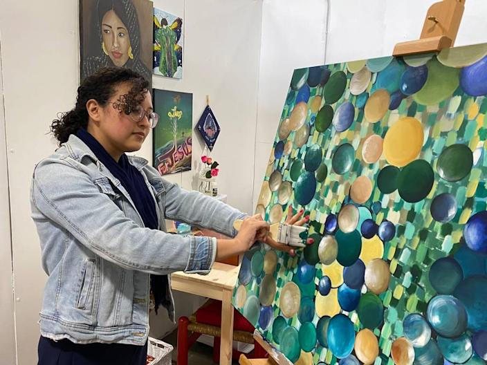 """Charlotte artist Rosa Renteria Jimenez paints in her studio at Charlotte Art League. """"The inspiration was bubbles. I was thinking about how beautiful and fragile they are. I was really comparing bubbles to people, to me, and how fragile we are, just like bubbles,"""" Jimenez said."""