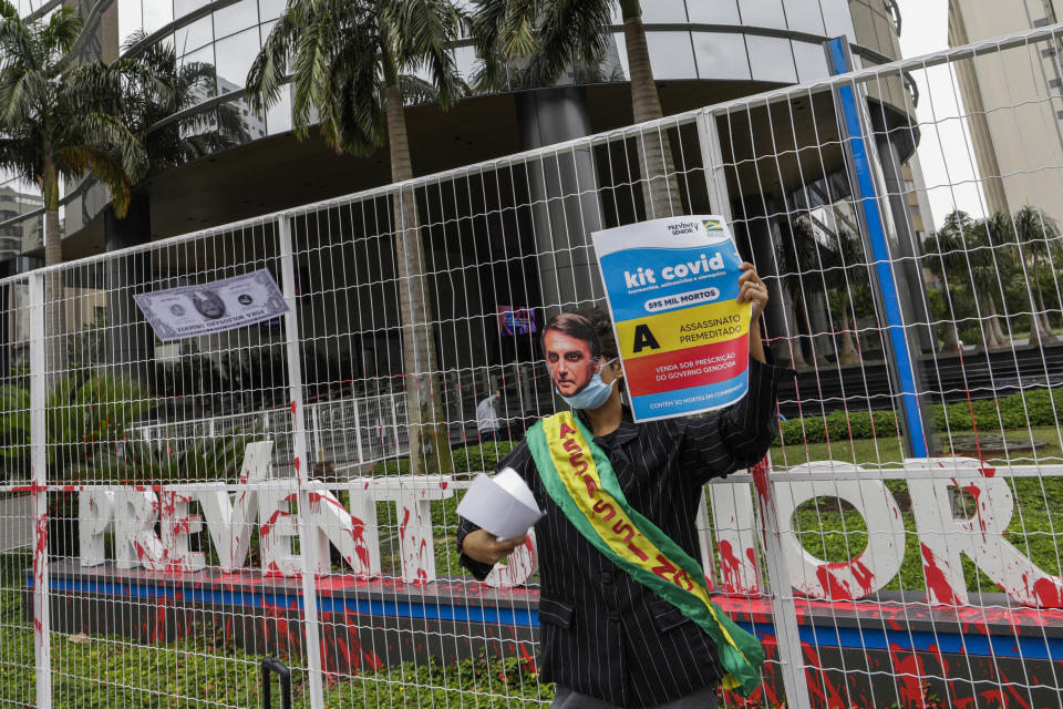 """A demonstrator in a Brazilian President Jair Bolsonaro mask protests against the Prevent Senior health care company outside its headquarters in Sao Paulo, Brazil, Sept. 30, 2021. Whistleblowing doctors, through their lawyer, testified at the Senate last week that Prevent Senior enlisted participants to test unproven drugs without proper consent and forced doctors to toe the line on prescribing unproven drugs touted by President Jair Bolsonaro as part of a """"COVID kit,"""" in the treatment of the new coronavirus. (AP Photo/Marcelo Chello)"""