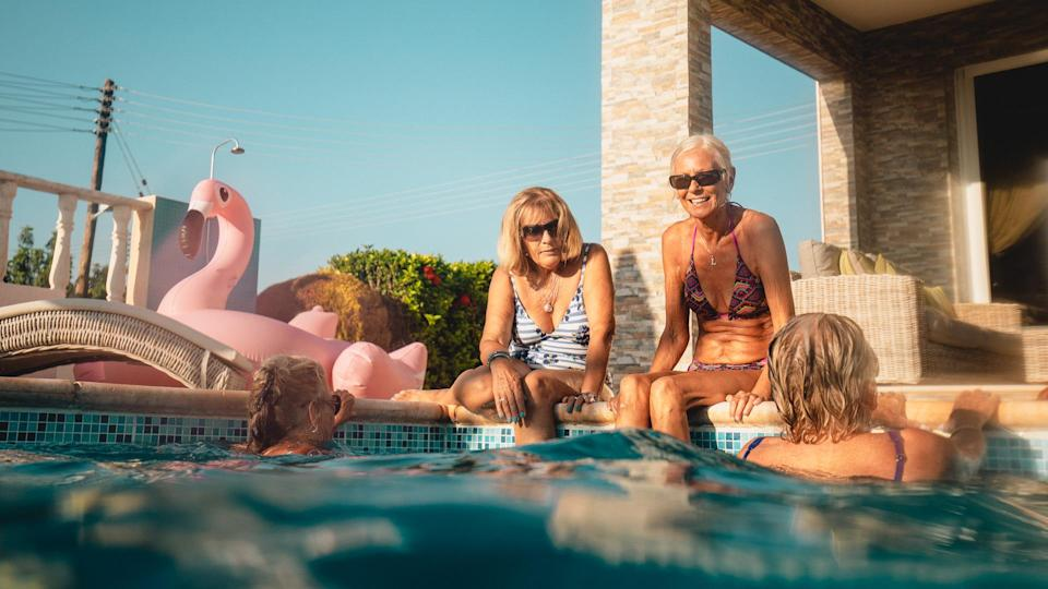 Group of senior women sitting by the side of the pool and relaxing in the pool while they talk.