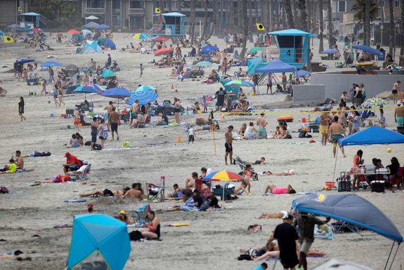 Few people wear masks as they gather at the beach in Oceanside, California, on 22 June.