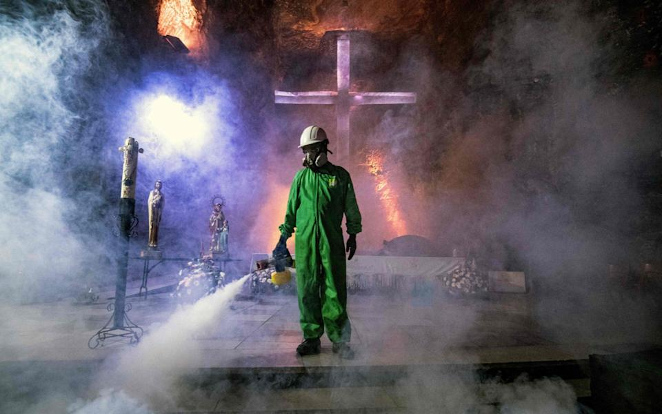 A worker disinfects the Salt Cathedral of Zipaquira, an underground church built into a salt mine, in Zipaquira, 45 km north of Bogota - JUAN BARRETO/AFP
