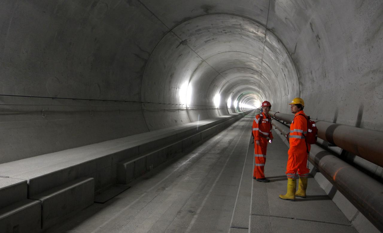 An employee of AlpTransit Gotthard Ltd and a visitor stand at the NEAT Gotthard Base tunnel near Erstfeld May 7, 2012. Crossing the Alps, the world's longest train tunnel should become operational at the end of 2016. The project consists of two parallel single track tunnels, each of a length of 57 km (35 miles)   REUTERS/Arnd Wiegmann   (SWITZERLAND - Tags: BUSINESS CONSTRUCTION EMPLOYMENT TRAVEL)