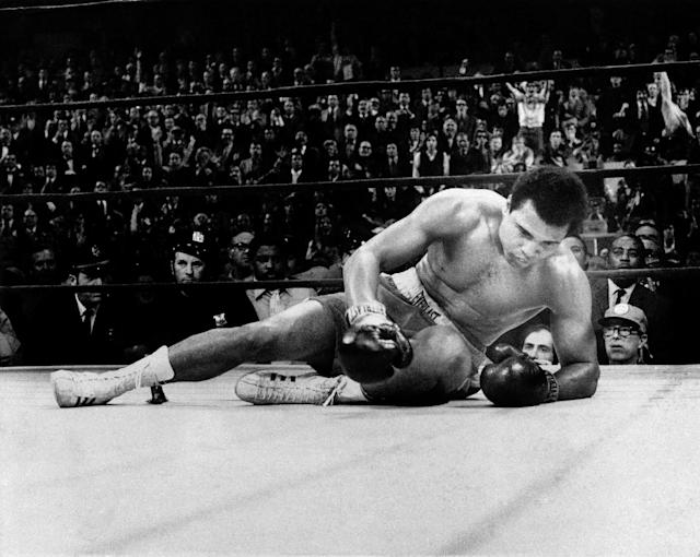 <p>Boxer Muhammad Ali crouches on the canvas as Joe Frazier circles in background (not seen) after Ali slipped during the 11th round of their title fight, March 8, 1971, New York. (AP Photo) </p>